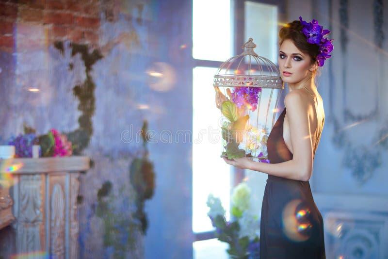Sehr schöne Brunettefrau mit Blumen in ihrem Haar hält lizenzfreies stockbild