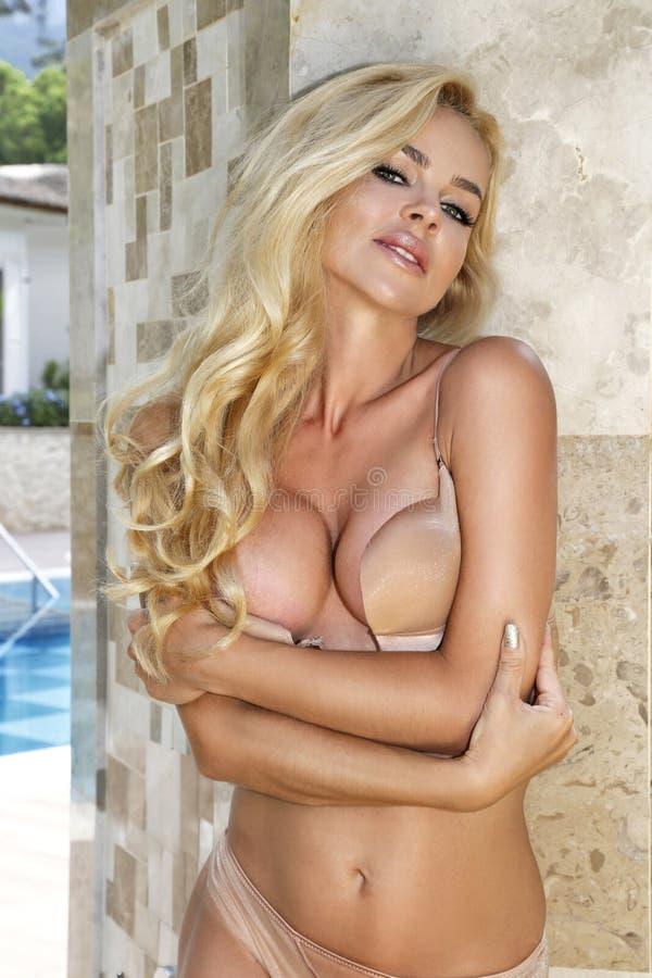 Sehr schöne sexy Blondine, welche die langhaarige Frau im sexy schwarzen Badeanzug auf dem schönen Swimmingpool steht stockbilder