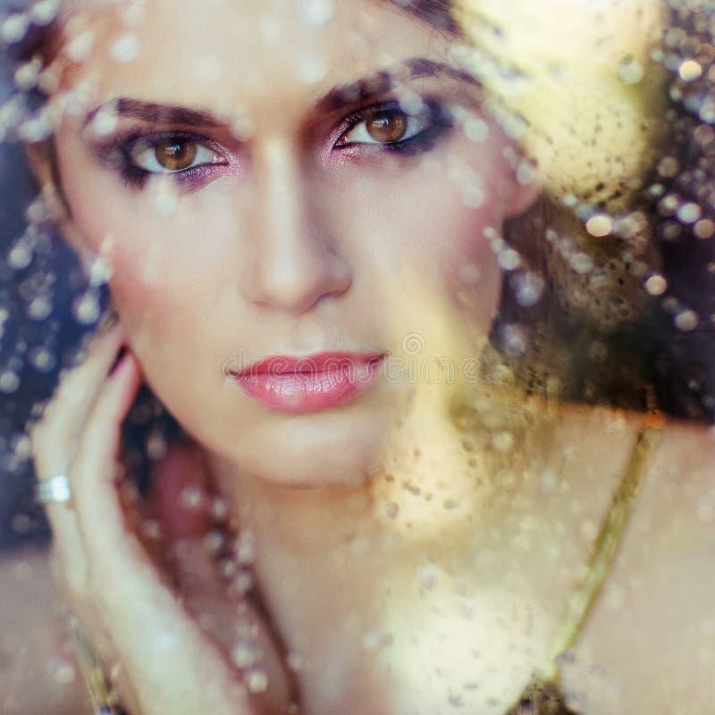 Sehr schöner Brunette mit braunen Augen hinter dem Glas, throug lizenzfreies stockfoto