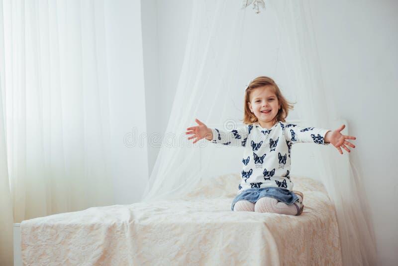 Sehr schönes blondes reizend kleines Mädchen, das im hellen Innenraum des Hauses, in der Vollansicht steht stockfotografie
