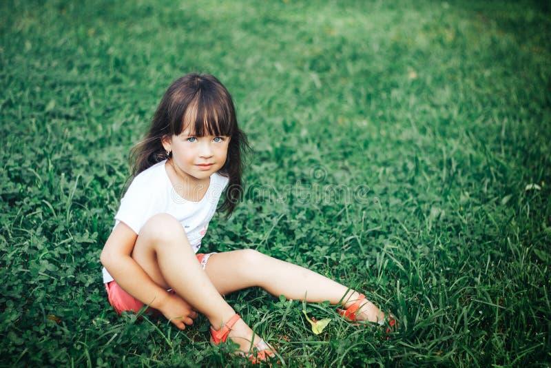 Sehr schönes kleines Mädchen, das auf Gras mit dem langen Haar betrachtet Kamera sitzt stockbild