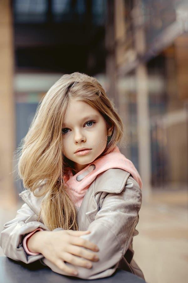 Sehr schönes kleines Mädchen mit dem langen blonden Haar, das draußen an einem Tisch sitzt stockfoto