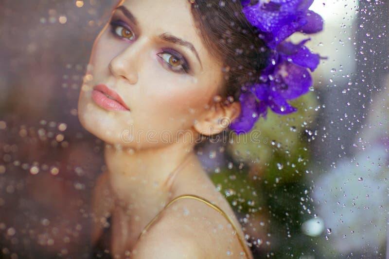 Sehr sinnliche schöne Brunettefrau mit Blumen in ihrem Haar b lizenzfreie stockbilder