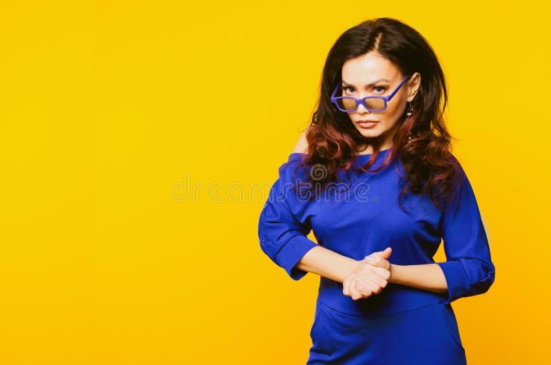 Sehr verärgerte reife Geschäftsfrau in der blauen Klage und Gläser, die zur Kamera schauen lizenzfreie stockfotos