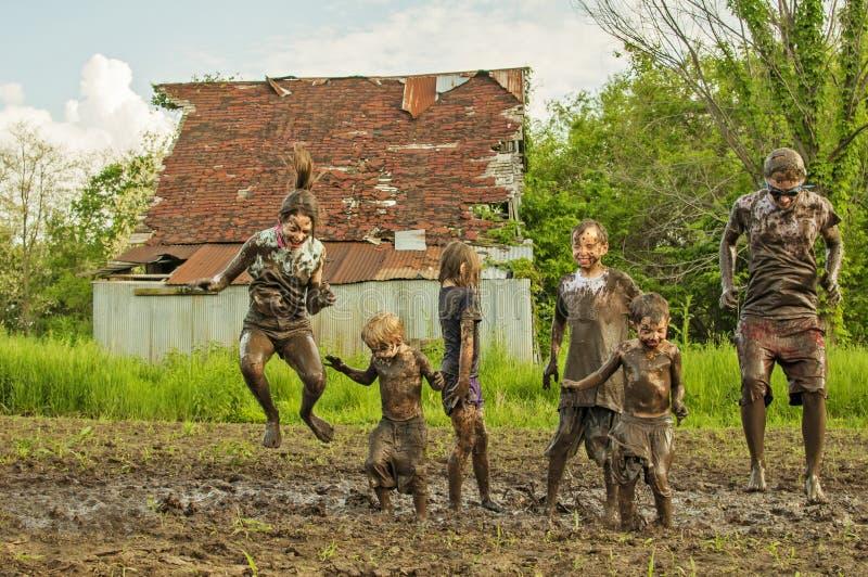 Sei bambini del paese che saltano nel fango immagini stock libere da diritti