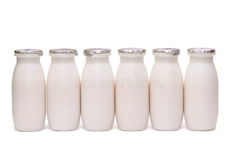 Sei bottiglie di plastica con latte isolato immagini stock