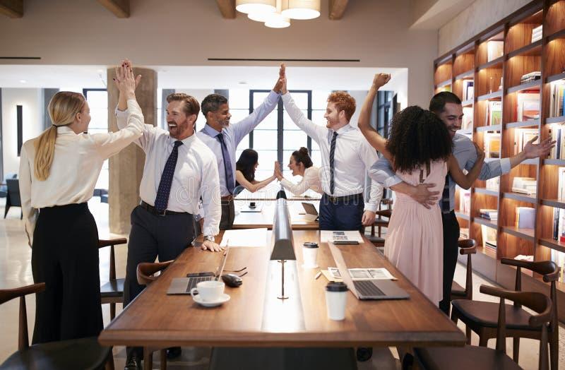 Sei colleghi che celebrano successo in un ufficio open space fotografia stock