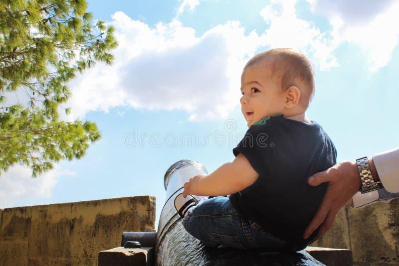 Sei mesi del neonato che si siede sul canone con l'aiuto di dady immagine stock libera da diritti