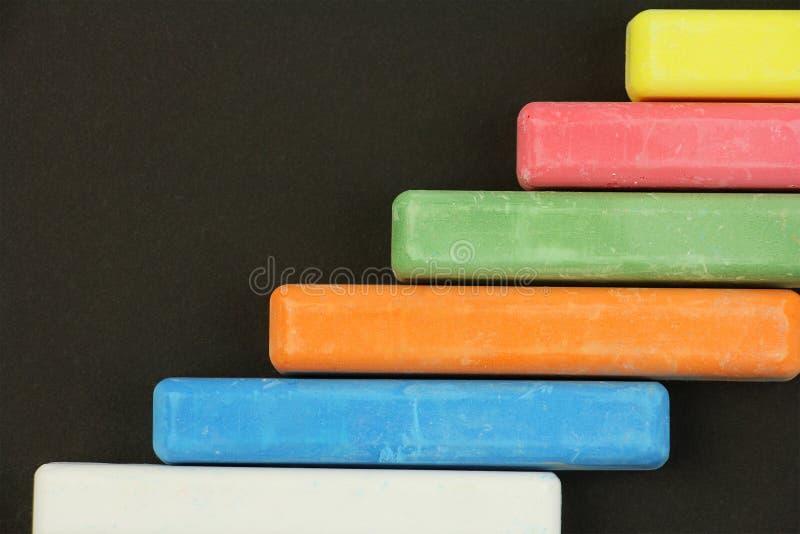 Sei pastelli colorati dei bambini su fondo nero, dalla destra, vista bianca e superiore giallo arancione verde rossa blu fotografia stock libera da diritti