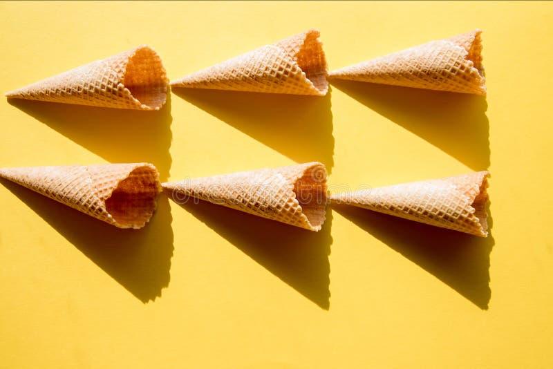 Sei tazze vuote della cialda per il gelato su un fondo giallo alla luce solare luminosa e ad ombre croccanti e dure immagine stock