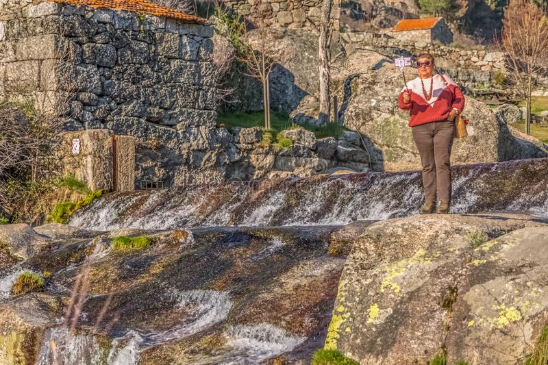 View of old woman taking pictures with mobile phone on stick, near the river with large granitic rocks royalty free stock photo