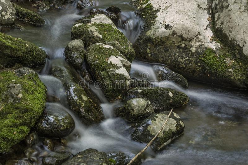 Seidiges Wasser, das über Moss Covered Rocks fällt lizenzfreie stockfotos