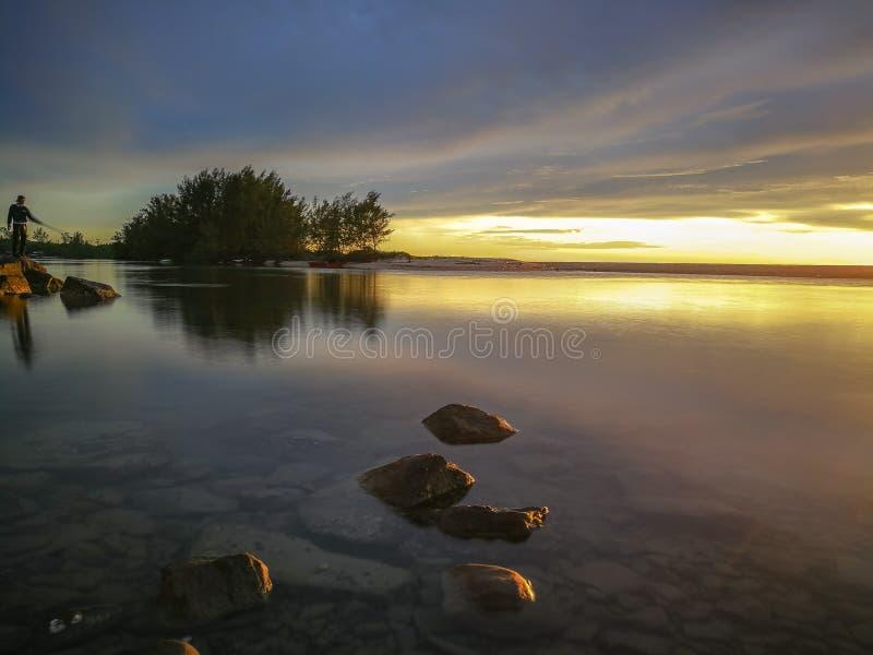 Seidiges Wasser verziert mit Fischern auf Sonnenuntergang scane lizenzfreies stockbild