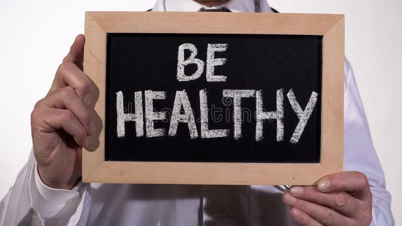 Seien Sie gesunder Text auf Tafel in Doktorhänden, Immunsystem, aktiver Lebensstil stockbild