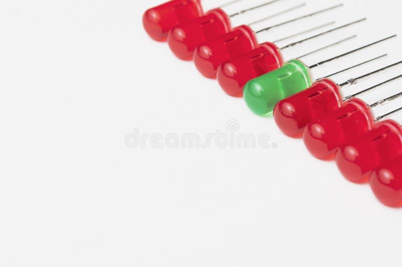 Seien Sie unterschiedlich und stehen Sie heraus vom Mengenkonzept: eine grüne LED zwischen acht roten einen Wei?er Hintergrund- u stockfotografie
