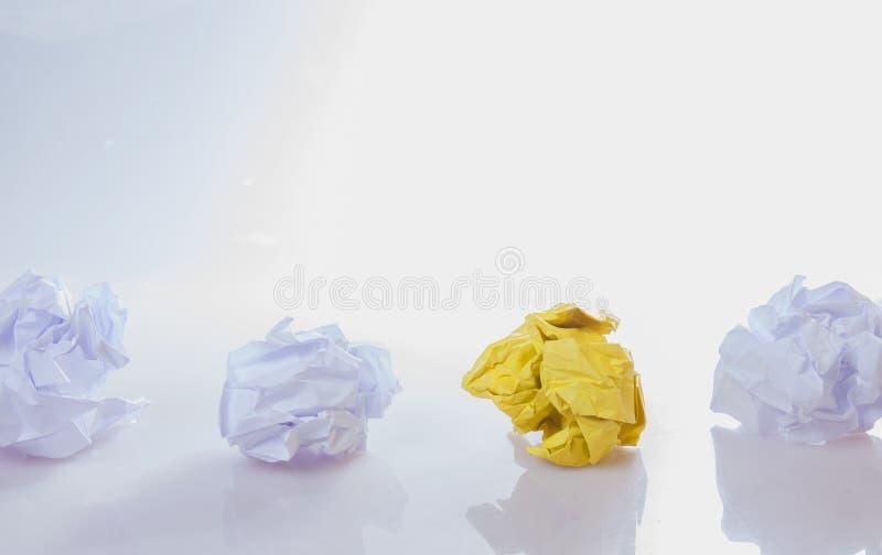 Seien Sie unterschiedliches Konzept Gelbe und weiße zerknitterte Papierbälle stockfotografie
