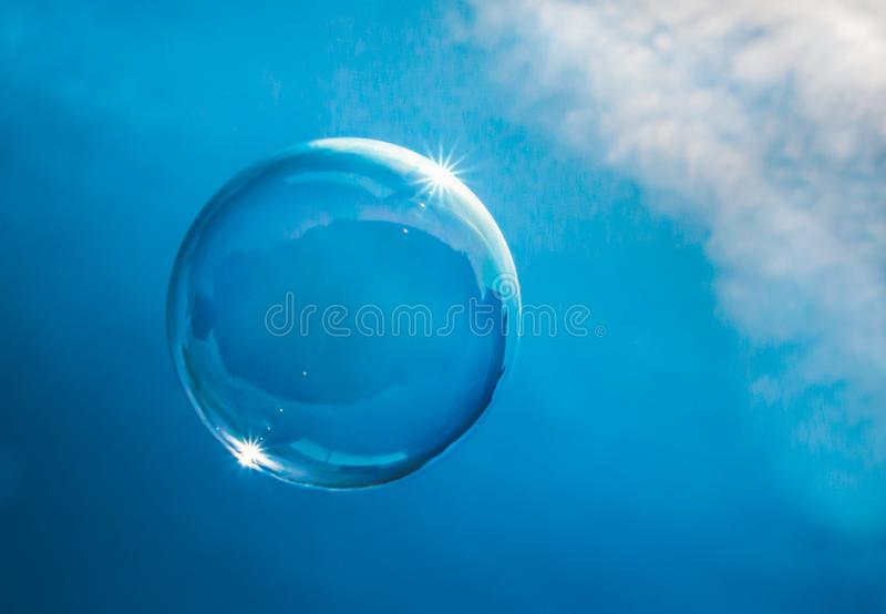 Seifenblase, die in einen blauen Himmel mit den Wolken fangen das Sonnenlicht schwimmt stockfotos
