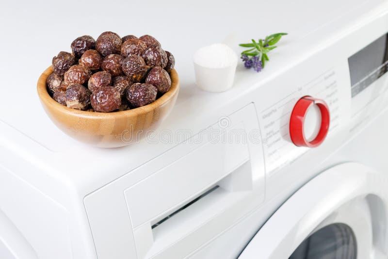 Seifennüsse in einer Schüssel auf der Waschmaschine und dem Lavendel, reinigendes Pulver, selektiver Fokus lizenzfreie stockbilder
