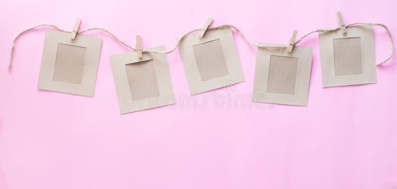 Seil, das mit leerem Papier, rosa Pastellpapier hängt Leerstelle für Ihr Textkonzept lizenzfreie stockfotos