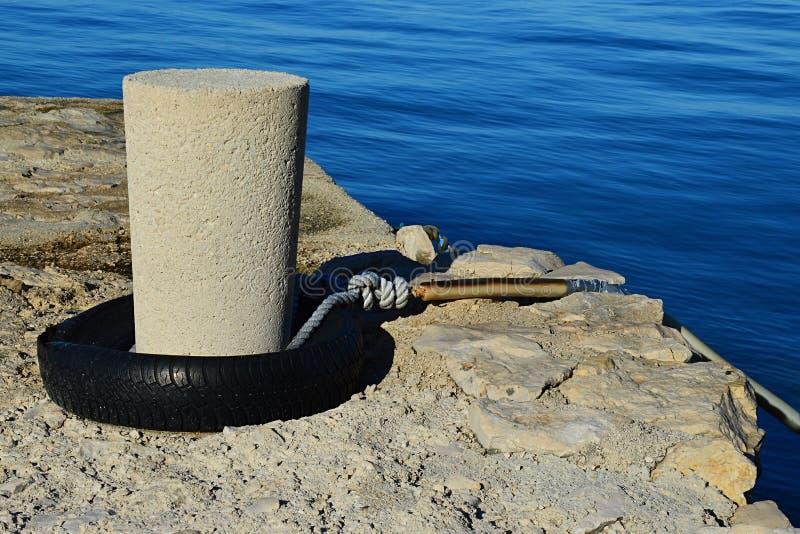 Seile mit gelb-schwarz gestreiftem Schutzschlauch, an Betonmolo-Rohren mit gebrautem Kfz-Kautschuk am Boden befestigt lizenzfreies stockfoto