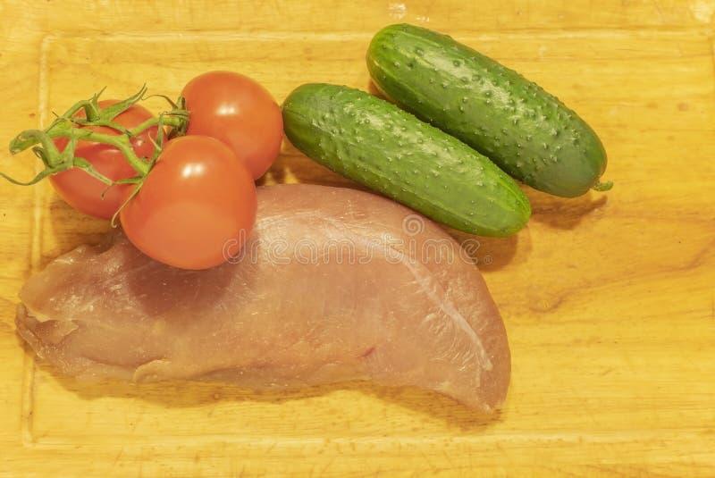 Sein de canard cru avec des tomates et des concombres Sur le hachoir images stock
