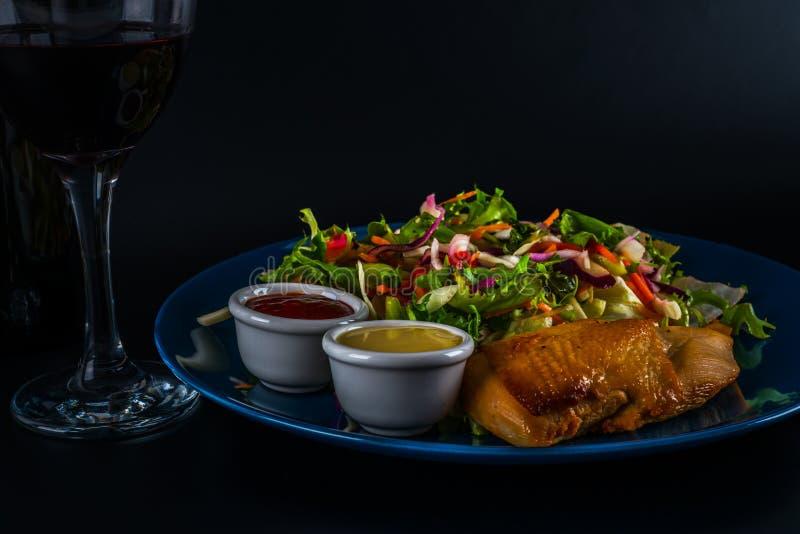 Sein de poulet rôti avec la préparation de laitue et deux sauces, plat bleu photographie stock libre de droits