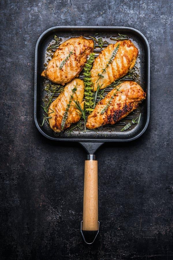 Sein rôti de poulet dans la casserole de gril avec les herbes et les épices fraîches sur le fond rustique foncé images stock