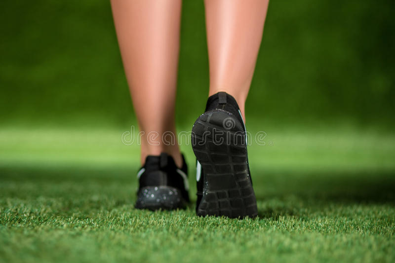 Seine Fußschönheit in den Schuhen auf einem Gras stockfoto