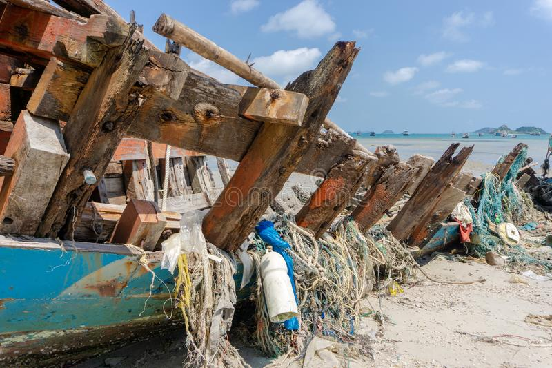 Seines or trawls or fishnets stuck on the old wooden keel of shipwreck that lay on the beach royalty free stock images