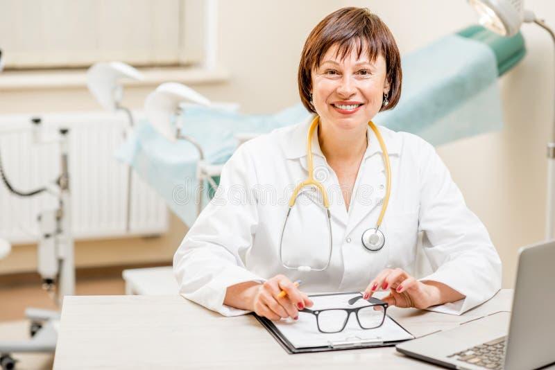 Seinor doktor som arbetar med bärbara datorn i det gynekologiska kontoret arkivbilder