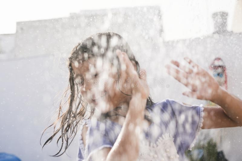Seis años el jugar borroso muchacha con agua fotografía de archivo