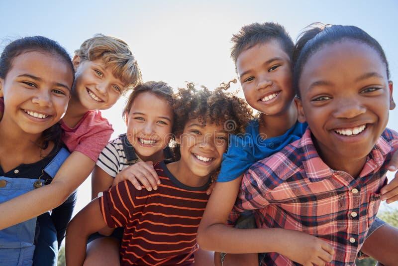 Seis amigos pre-adolescentes que llevan a cuestas en un parque, cierre encima del retrato imagen de archivo libre de regalías