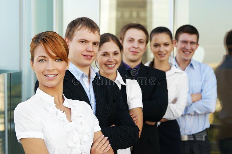 Seis businesspersons jovenes se están colocando en una fila fotos de archivo libres de regalías