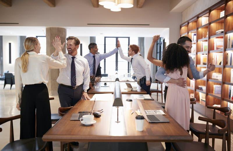 Seis colegas que celebran éxito en una oficina abierta del plan imágenes de archivo libres de regalías