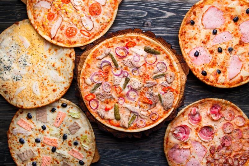Seis diversas pizzas fijaron para el menú en la tabla de madera Alimento italiano fotografía de archivo