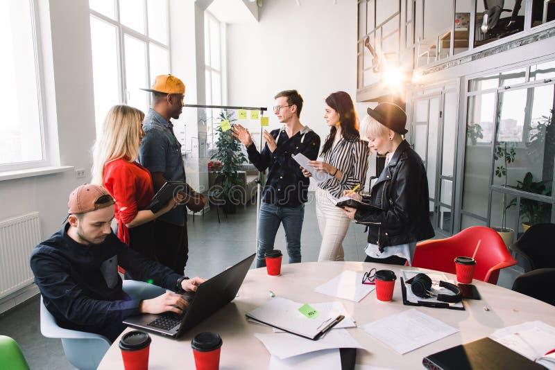 Seis empresarios jovenes en ropa de sport que discuten y concepto de planificación Frente del marcador y de las etiquetas engomad fotografía de archivo libre de regalías