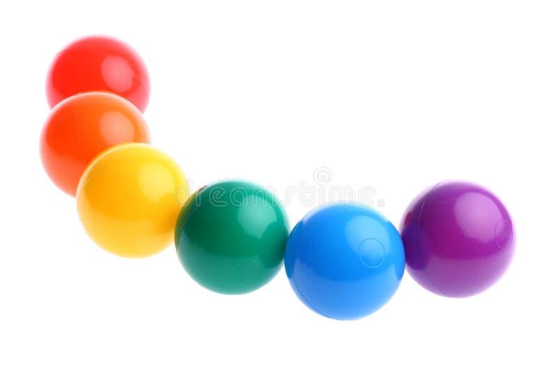Seis esferas plásticas coloridas brilhantes do brinquedo na fileira fotos de stock royalty free