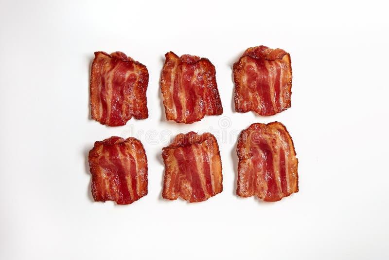 Seis fatias de bacon fritado fresco alinhado em seguido imagens de stock royalty free