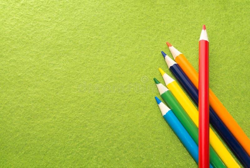 Seis lápis coloridos em um fundo sentido verde Lápis coloridos diferentes com espaço para o texto De volta à escola Lições da art imagens de stock