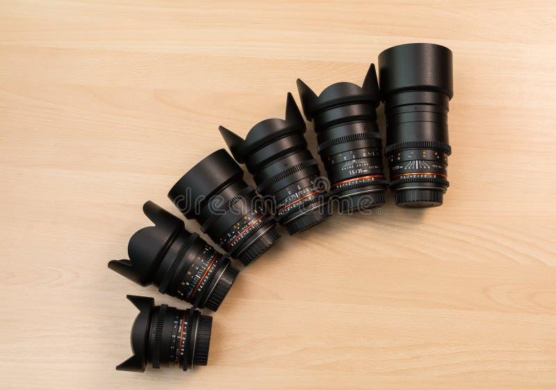 Seis lentes con diversas longitudes focales mienten en una superficie de madera Película usando cámaras de DSLR imagen de archivo libre de regalías