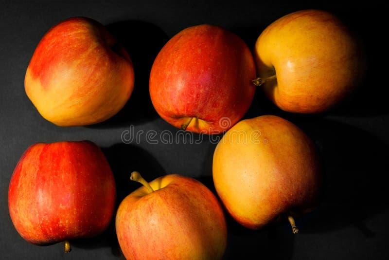 Seis manzanas rojas maduras ponen en fondo negro Color rojo, color amarillo Comida vegetariana Alimento sano Manzanas preparadas fotos de archivo libres de regalías