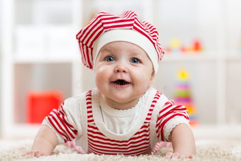 Seis meses del bebé que miente en la alfombra en piso en cuarto de niños fotografía de archivo libre de regalías
