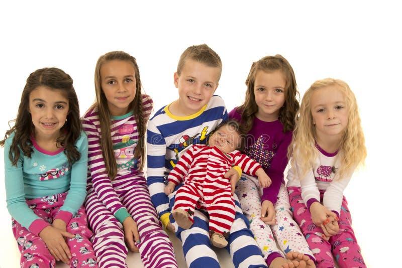 Seis niños adorables que llevan la sonrisa de los pijamas de la Navidad feliz foto de archivo