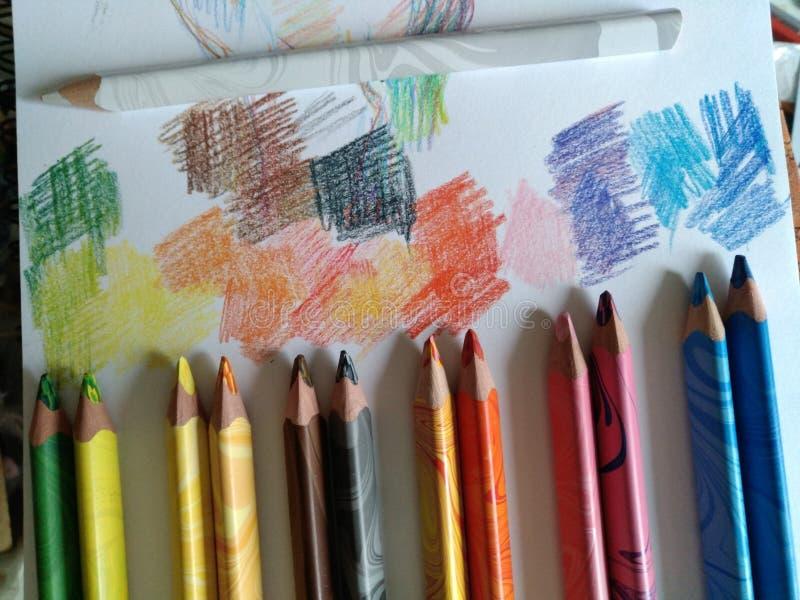 Seis pares de lápices coloreados mienten al lado del intervalo, pintando en el papel con los puntos coloreados, ambiente creativo imagen de archivo libre de regalías