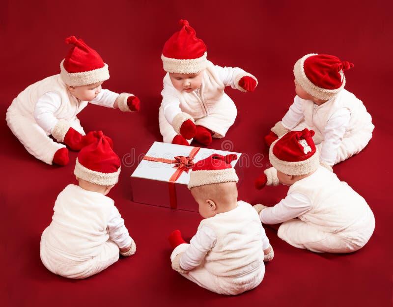 Seis pequeños ayudantes de santa están examinando el regalo de la Navidad fotos de archivo libres de regalías