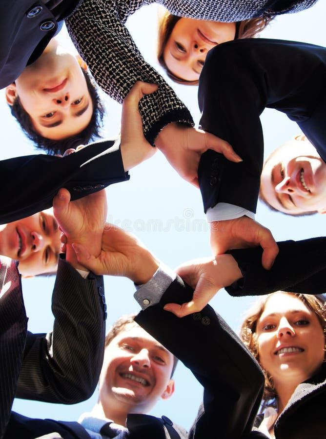 Seis pessoas novas do negócio que mantêm as mãos unidas fotografia de stock