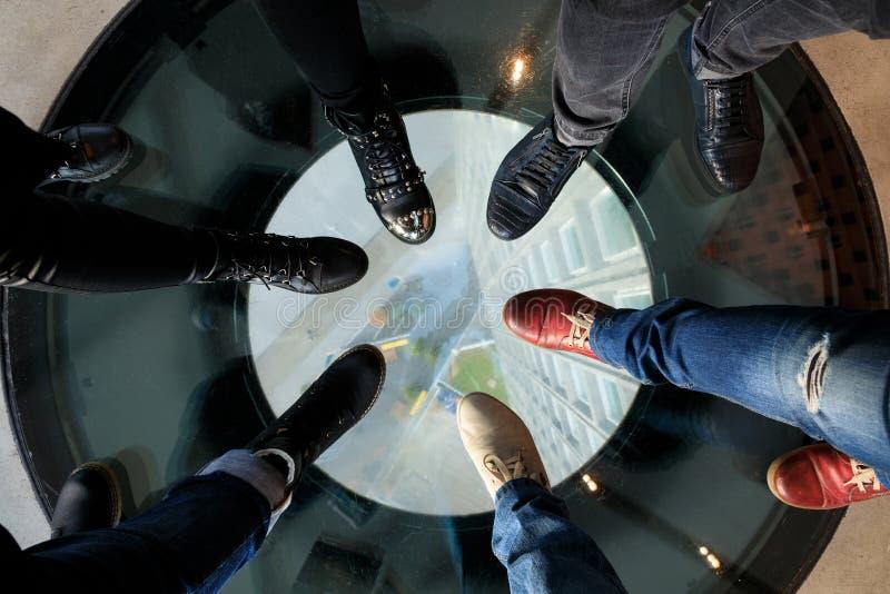 Seis piernas en el piso de cristal fotografía de archivo