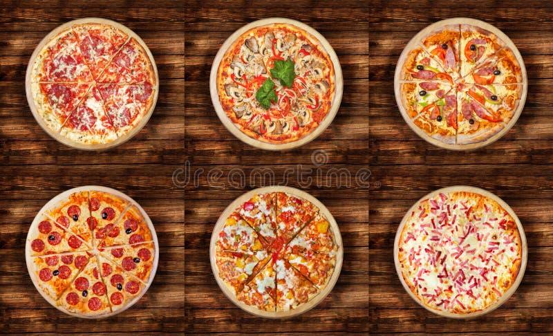 Seis pizzas diferentes ajustaram-se para o menu na tabela de madeira Culinária tradicional do alimento italiano Pizzas da carne c foto de stock royalty free