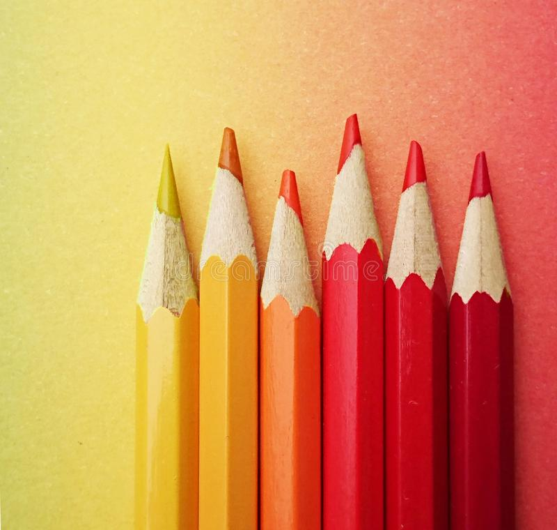 Seis plumas coloridas dispuestas en los colores amarillos y rojos en el papel colorido en el curso del arco iris fotos de archivo
