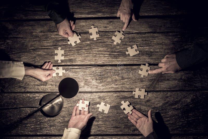 Seis sócios comerciais que colocam partes do enigma em um círculo imagens de stock royalty free